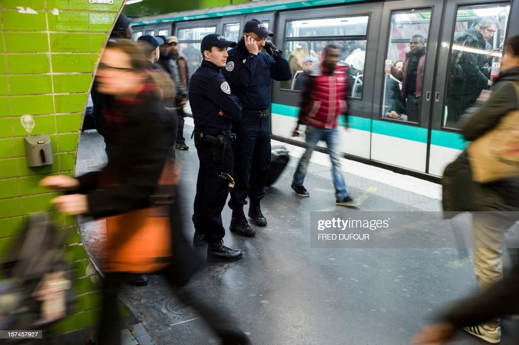 A policeman talks on a cell phone during a patrol in the metro station of the Gare du Nord (North railway station) in Paris on November 29, 2012 . AFP PHOTO / FRED DUFOUR