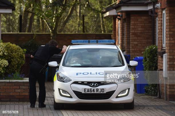 A policeman talks to a colleague parked in a gated housing estate in West Didsbury North west England connected to Westminster terrorist Khalid...