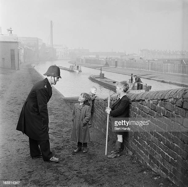 A policeman talks to a group of children on a canal bridge in Birmingham 1954 Original publication Picture Post 6979 The Best And The Worst Of...