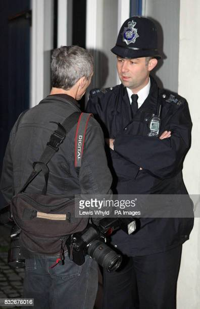 A policeman talks to a photographer outside Kate Middleton's house before Kate Middleton is met by photographers outside her house in London on her...
