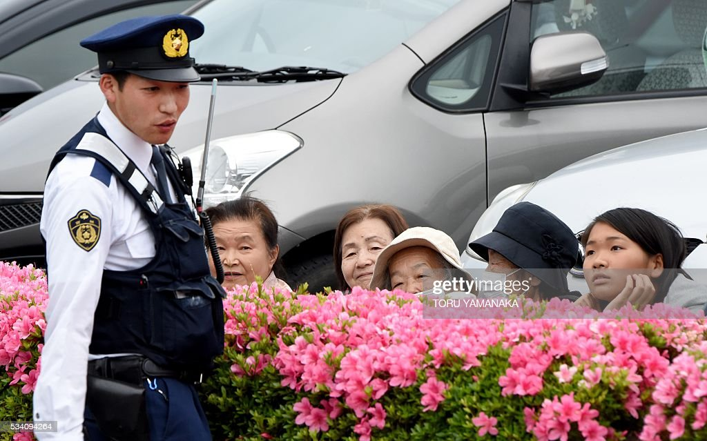A policeman talks with residents who gathered on the street to see leaders of the Group of Seven (G7) summit meeting in Shima, Mie prefecture, on May 25, 2016. Japan is on high-alert ahead of a Group of Seven summit with thousands of police on the streets of Tokyo and fanning out across the country as authorities boost security to unprecedented levels. / AFP / TORU