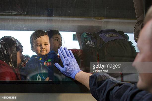 A policeman touches the window playing with a child while migrants take a bus after arriving on an ICE highspeed train of Deutsche Bahn from Munich...
