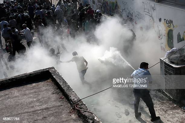 A policeman tries to disperse hundreds of migrants by spraying them with a fire extinguisher during a gathering for a registration procedure at the...