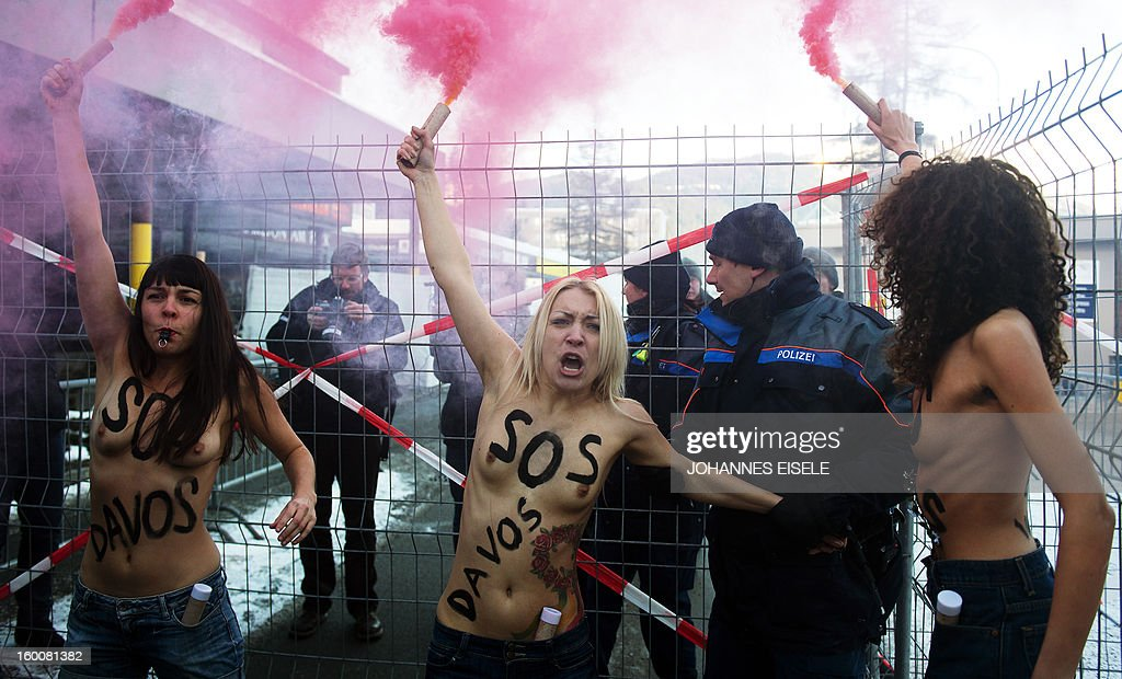 A policeman tries to prevent activists of the Ukrainian feminist group FEMEN from shouting slogans during a topless protest on January 26, 2013, against the World Economic Forum (WEF) 2013 annual meeting in the Swiss resort of Davos. AFP PHOTO / JOHANNES EISELE