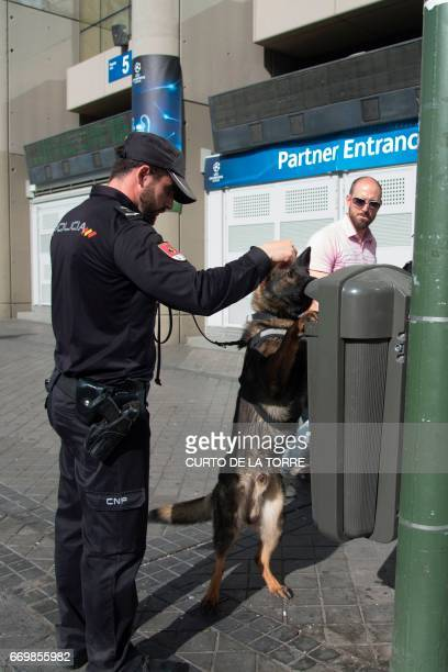 A policeman uses a police dog to check a rubbish bin outside the stadium before the UEFA Champions League quarterfinal second leg football match Real...