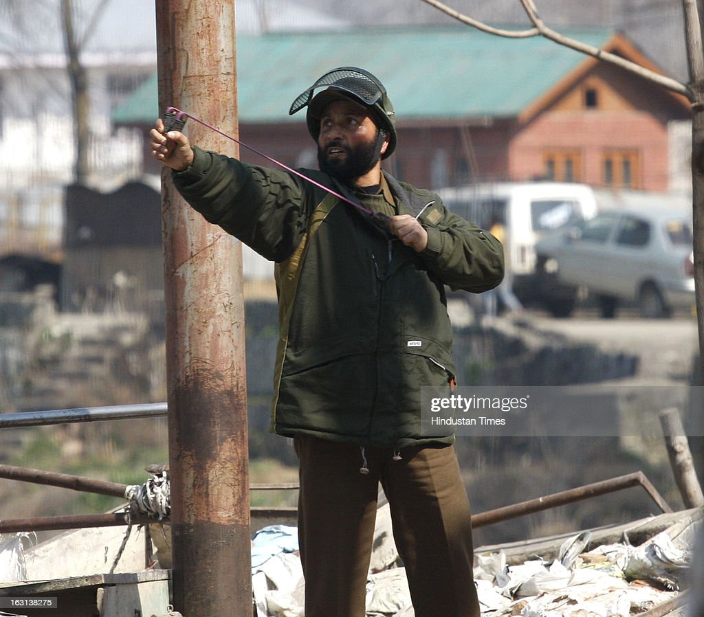 Policeman uses a sling against Kashmiri protersters as they clash during a strike to protest the death of 28 year old Kashmiri student, Mudassir Qamran Malla in the city of Hyderabad on March 5, 2013 in Srinagar, India. Most shops, business establishments remained closed in Kashmir valley.