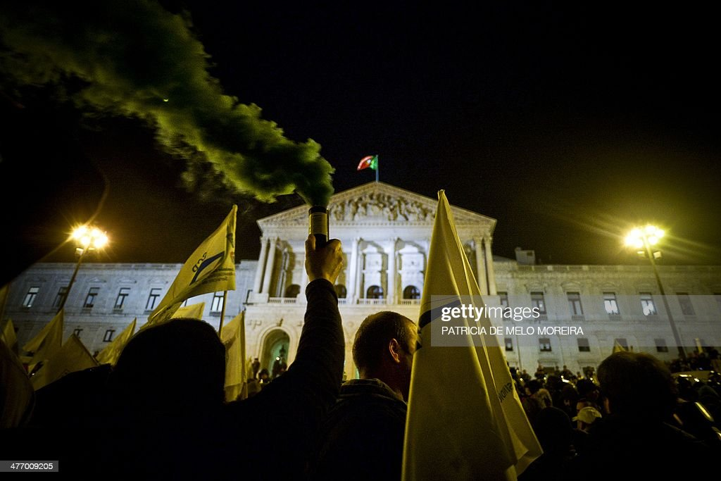 A policeman uses a smoke canister as members of the Portuguese police protest against the government's austerity measures outside the Portuguese Parliament in Lisbon on March 6, 2014. Thousands of police protested in Lisbon late over pay cuts imposed by the government as part of an austerity drive to roll back public debt. 'Since January they've taken 200 euros ($280) from my monthly pay. And I'm not even counting the pay-cuts over the past three years,' said one officer from the centre of the country, Antonio Ferreira. AFP PHOTO/ PATRICIA DE MELO MOREIRA