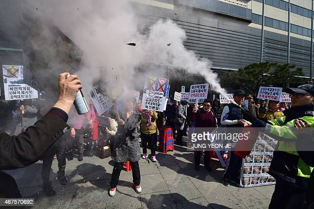A policeman uses an extinguisher as South Korean conservative activists burn a portrait of North Korean leader Kim JongUn during an antiNorth Korea...