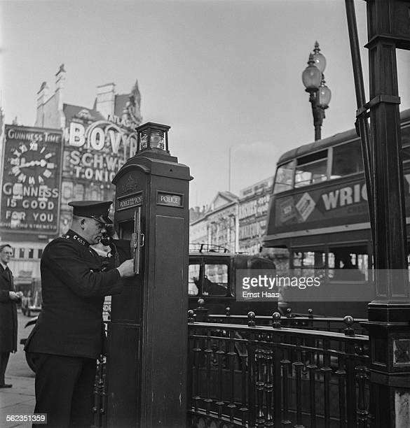 A policeman using a police box in Piccadilly Circus London circa 1953