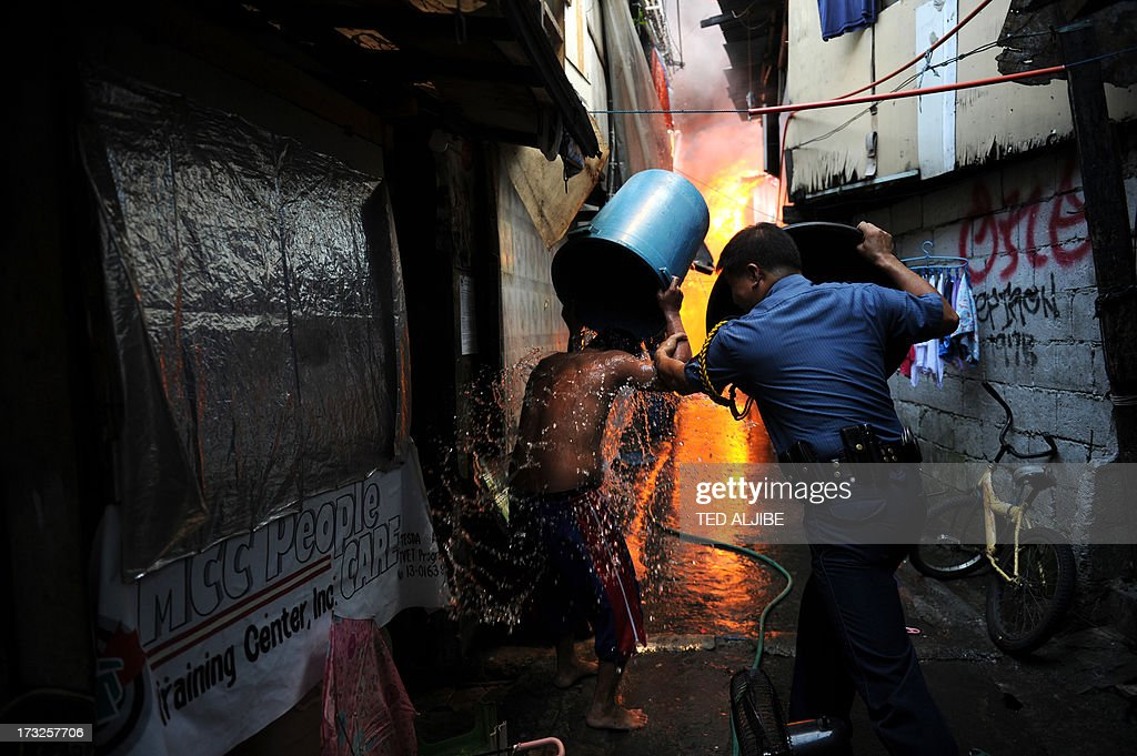 A policeman (R) using a wash basin to protect himself from the heat as he persuades a resident to leave next to burning houses after a fire engulfed a shanty town at the financial district of Manila on July 11, 2013. There were no immediate reports of casualties from the blaze, which occurred mid-morning amid government plans to relocate thousands of families living in areas vulnerable to floods and typhoons.