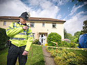 Policeman using walkie talkie outside house with forensic scientists in background at crime scene