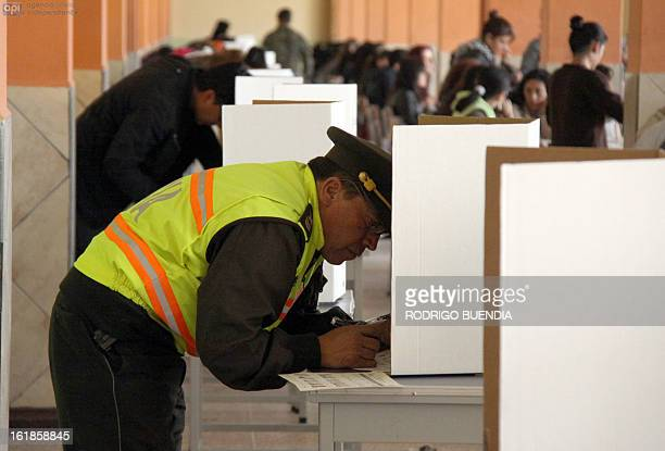 A policeman votes at a polling station in Quito on February 17 2013 Ecuadoreans began voting Sunday in national elections in which President Rafael...