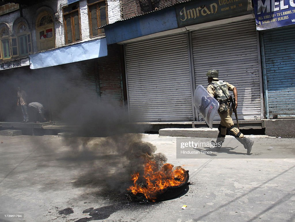 Policeman walk near a burning tire during a protest against killing of 4 people in BSF firing on July 18, 2013 in Srinagar, India. Four people were killed today when security personnel opened fire at a mob that had gathered at a BSF camp in Ramban district protesting against alleged manhandling of an Imam of the area by the force. Curfew would be imposed in Srinagar and all other major towns in the Kashmir Valley from Friday morning as a precautionary measure.