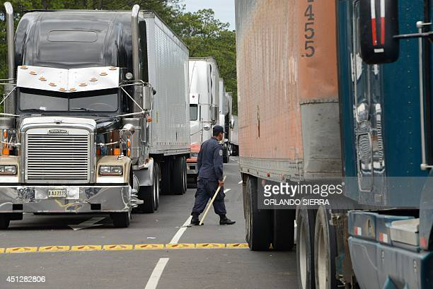 A policeman walks amidy iddle lorries along the San Pedro SulaTegucigalpa road on June 26 2014 during a road hauliers strike against a road toll AFP...