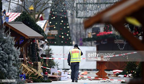 TOPSHOT A policeman walks at the Christmas market near the KaiserWilhelmGedaechtniskirche the day after a terror attack in central Berlin on December...