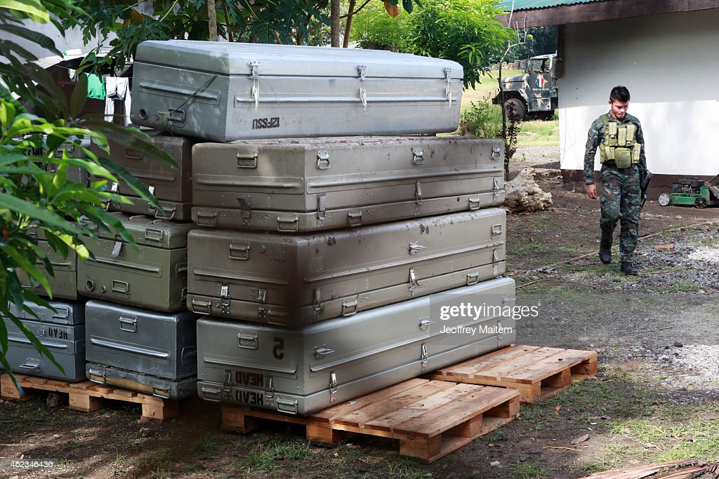 A policeman walks beside metal caskets on January 27, 2015 inside a military morgue in Datu Odin Sinsuat, Maguindanao Province, Philippines. Dozens of elite policemen were killed after a clash with a Muslim rebel group. Lawmen were trying to serve arrest warrants on January 25, 2015 for criminals led by Malaysian bomb maker Zulkifli bin Hir, known in military and police officials as Marwan, when the group clashed with the guerillas under Commander Guiawan of Bangsamoro Islamic Freedom Fighters, a breakaway group of the Moro Islamic Liberation, the countrys largest rebel group engaged in peace talks with Manila. The death toll of government fatalities in the fierce firefight reached fifty.