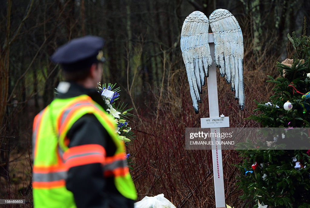 A policeman walks by a makeshift shrine to the victims of an elementary school shooting in Newtown, Connecticut, December 17, 2012. Funerals began Monday in the little Connecticut town of Newtown after the school massacre that took the lives of 20 small children and six staff, triggering new momentum for a change to America's gun culture. The first burials, held under raw, wet skies, were for two six-year-old boys who were among those shot in Sandy Hook Elementary School. On Tuesday, the first of the girls, also aged six, was due to be laid to rest. There were no Monday classes at all across Newtown, and the blood-soaked elementary school was to remain a closed crime scene indefinitely, authorities said. AFP PHOTO/Emmanuel DUNAND