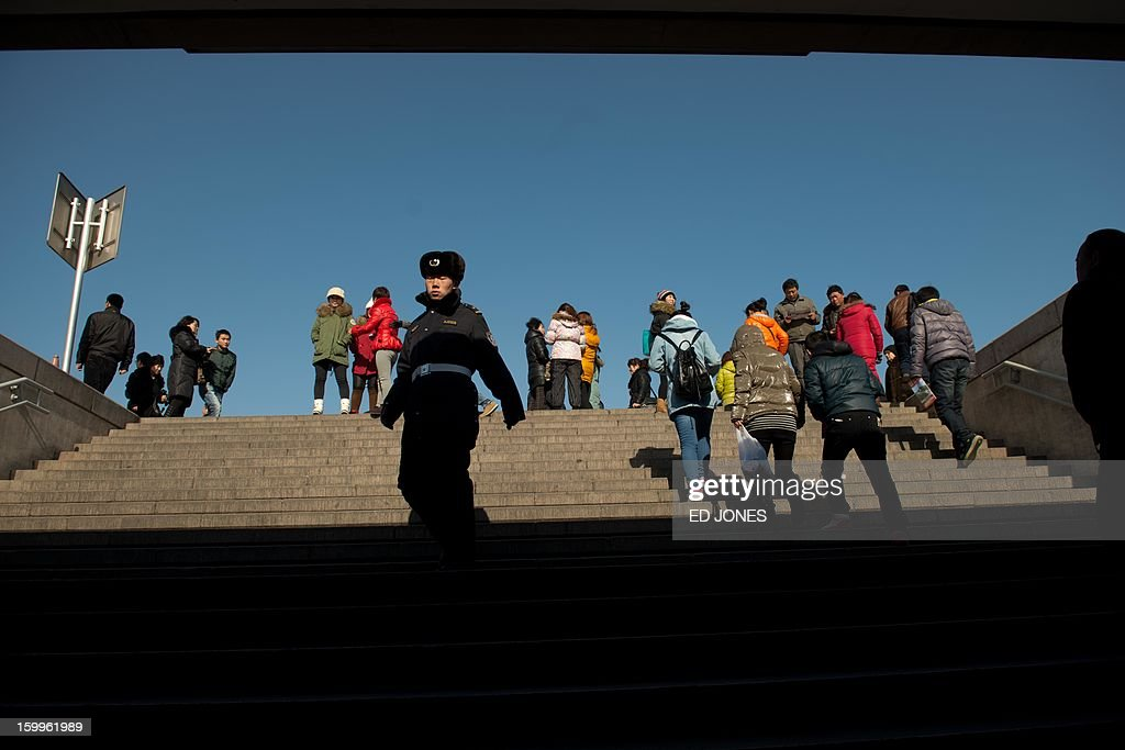 A policeman walks down stairs past tourists making their way to Tiananmen Gate in Beijing on January 24, 2013. China's manufacturing activity expanded in January at its fastest pace in two years, HSBC said, the latest sign of recovery in the world's second biggest economy. AFP PHOTO / Ed Jones