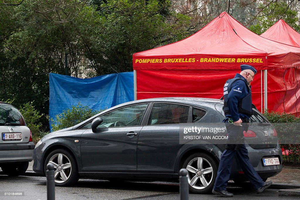 A policeman walks near the site where a corpse of a child was found, on February 14, 2016, near the rue Van Hammee in Schaarbeek-Schaerbeek in Brussels. / AFP / Belga / KRISTOF VAN ACCOM / Belgium OUT