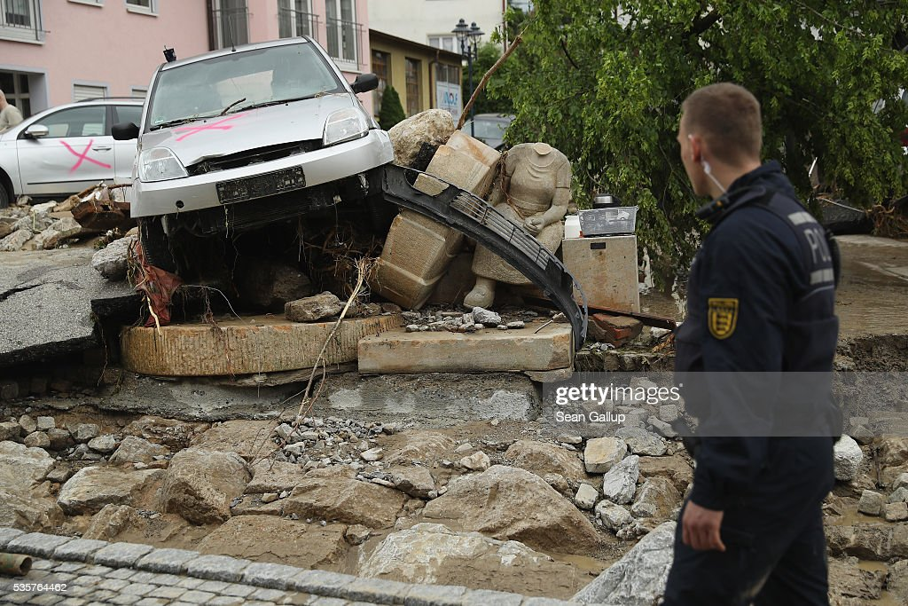 A policeman walks past a headless monument and smashed car in the village center following a furious flash flood the night before on May 30, 2016 in Braunsbach, Germany. The flood tore through Braunsbach, crushing cars, ripping corners of houses and flooding homes during a storm that hit southwestern Germany. Miraculously no one in Braunsbach was killed, though three people died as a result of the storm in other parts of the country.