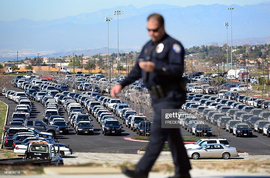 A policeman walks past a parking lot full of police vehicles as police officers, friends and family attend a memorial service for slain Riverside police officer Michael Crain at the Grove Community Church in Riverside, California, on February 13, 2013. Law enforcement personnel from across the state, including local dignitaries, military veterans, colleagues, friends and loved ones of Crain gathered to pay their final respects to the policeman killed last week in what the city's police chief described as a 'cowardly ambush.'' Crain was fatally shot February 7 when he and his partner ran afoul of fugitive Christopher Jordan Dorner. AFP PHOTO / Frederic J. BROWN