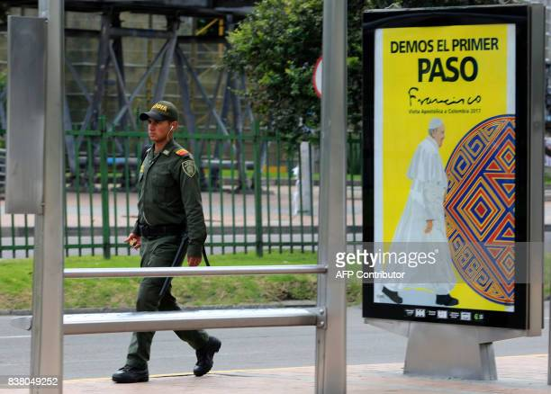 A policeman walks past a sign reading 'Let's all take the first step' ahead of Pope Francis' upcoming visit in Bogota on August 23 2017 Pope Francis...