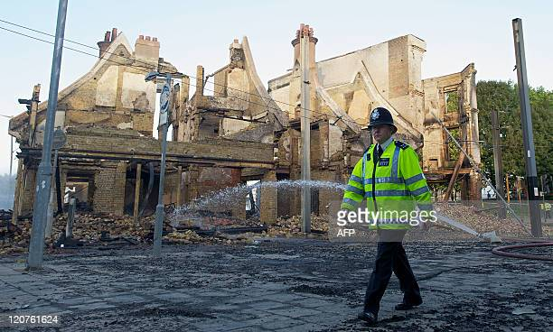A policeman walks past the charred remains of the Reeves furniture store in Croydon south of London on August 9 following a third night of violence...