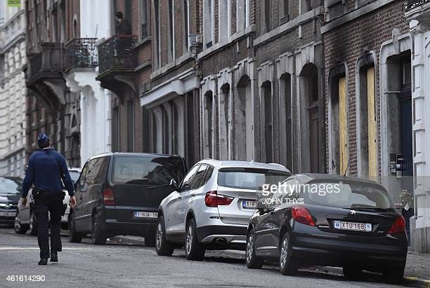 A policeman walks past the house attacked at Colline street in Verviers eastern Belgium on January 16 after police shot dead two suspects in a gun...