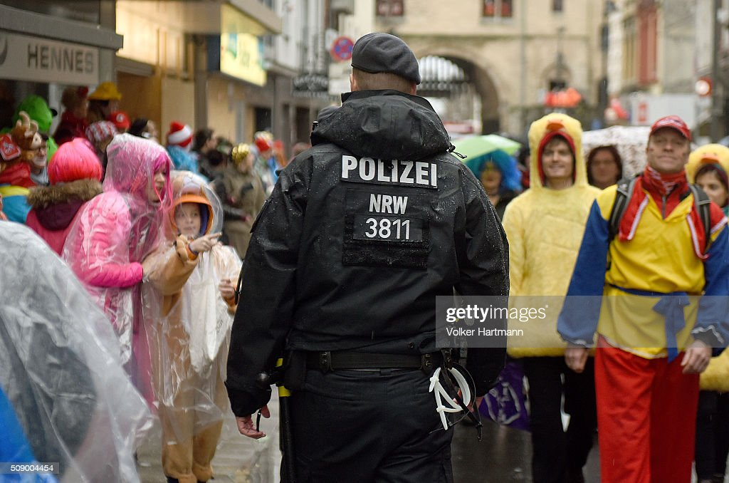 A Policeman walks through Carnival revellers during the annual Rose Monday parade on February 8, 2016 in Cologne, Germany. The centuries-old tradition of German carnival occurs in February and runs until Ash Wednesday, the start of Lent, and culminates in Rose Monday celebrations. Police are on added alert this year, particularly in Cologne, due to the New Year`s Eve sex attacks on women that have been attributed to gangs of migrants.