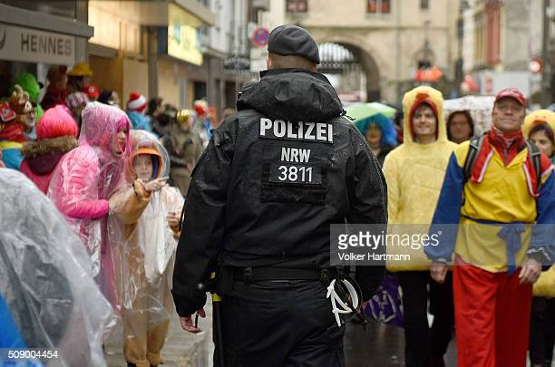 Policeman walks through Carnival revellers during the annual Rose Monday parade on February 8 2016 in Cologne Germany The centuriesold tradition of...