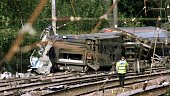 A policeman walks towards the carriages which overturned after the London to Leeds train derailed near Hatfield thirty miles north of London 17...