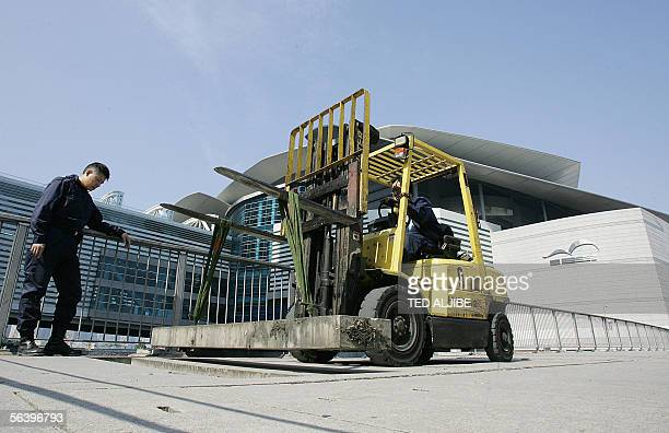A policeman watches as a worker covers a hole of a bridge using a forklift after inspection in front of Convention and Exhibition center in Hong Kong...
