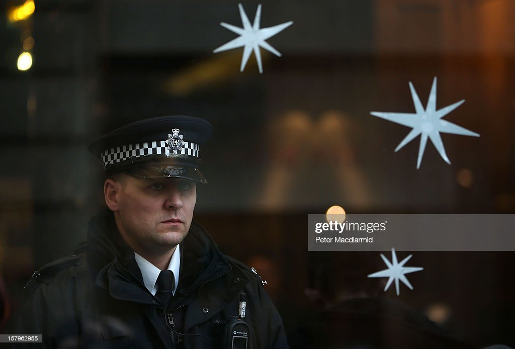 A policeman watches from inside a Starbucks coffe shop as UK UNCUT supporters protest outside on December 8, 2012 in London, England. UK UNCUT are holding a day of protests at various Starbucks throughout the United Kingdom after the coffe chain were revealed to be paying almost no corporation tax.