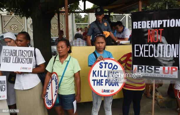 A policeman watches protesters and relatives as they hold a rally outside the office of the antigraft body in Manila on March 14 while a woman who...