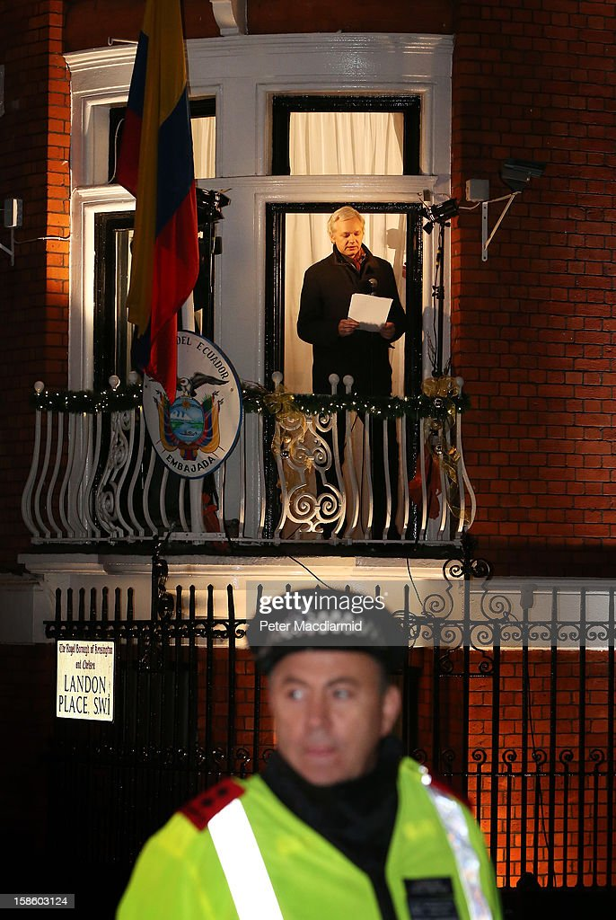 A policeman watches the crowd as Wikileaks founder Julian Assange speaks from the Ecuadorian Embassy on December 20, 2012 in London, England. Mr Assange has been living in the embassy since June 2012 in an attempt to avoid extradition to Sweden where he faces allegations of sexual assault.
