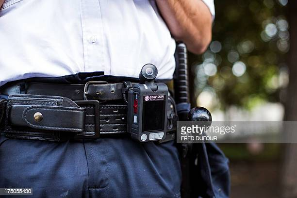 A policeman wears a camera system used for identity checks and as evidence in case of litigation during a patrol in the street on July 30 2013 in...