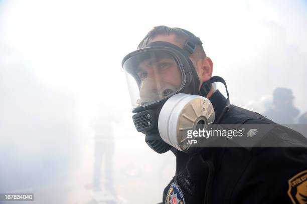 A policeman wears a gas mask during clashes at a May Day demonstration on May 1 2013 in Istanbul Turkish riot police used water cannon and tear gas...