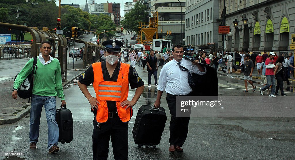 A policeman wears a protective mask on December 6, 2012 in Buenos Aires. Several buildings in downtown Buenos Aires were evacuated when a fire in a container loaded with a chemical substance near the port area released a toxic cloud with a strong stench, the Civil Defense said. AFP PHOTO/STR