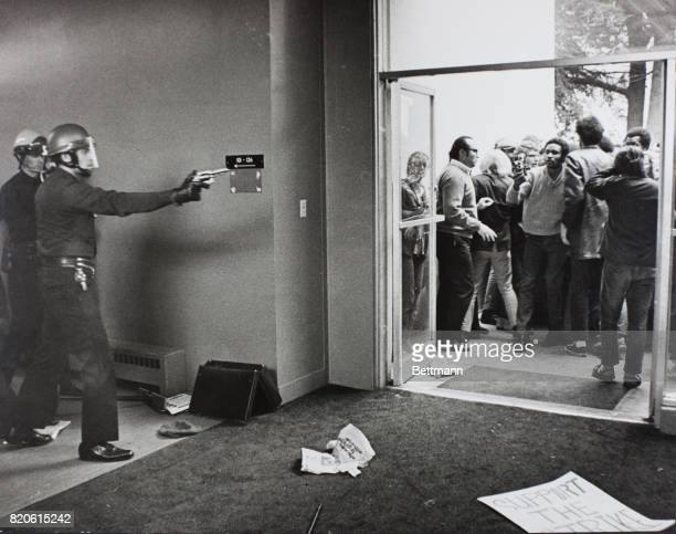 Policeman with a drawn gun holds back antiwar demonstrators who attacked the Administration Building at San Francisco State College They were also...