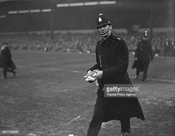 A policeman with a goose that a fan had let loose on the pitch at Molineux during the Fourth Round FA Cup tie between Wolverhampton Wanderers and...