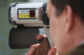 A policeman with a radar gun monitors cars for speeding during a citywide police action to catch people for speeding and other traffic infringements...