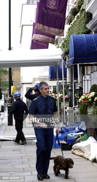 A policeman with a sniffer dog as workmen erect a screen outside the entrance to The Goring hotel which Kate Middleton has chosen as a base for...