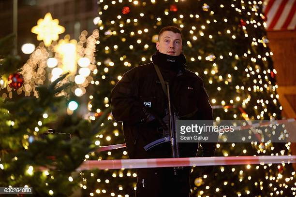 A policeman with a submachine gun stands at the area after a lorry truck ploughed through a Christmas market on December 19 2016 in Berlin Germany...