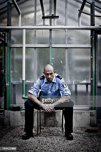 Polizist mit bald head befindet sich in einem alten verlassenen greenhouse