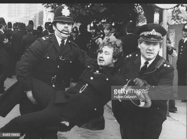 A policeman with blood streaming down his face being helped to safety by colleagues in New Cross London after a clash between political demonstrators...