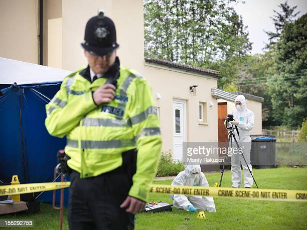Policeman with forensic scientists outside house at crime scene
