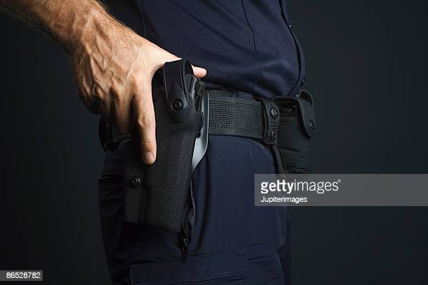 Policeman with hand on gun holster