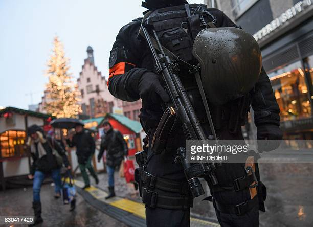 A policeman with machine gun stands guard at the Christmas market at the Roemerberg in the centre of Frankfurt am Main western Germany on December 22...