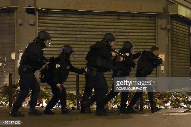 Policemen advance in combat position near 'Le petit Cambodge' restaurant one of the site of the attacks in Paris after a crowd movement that led to a...