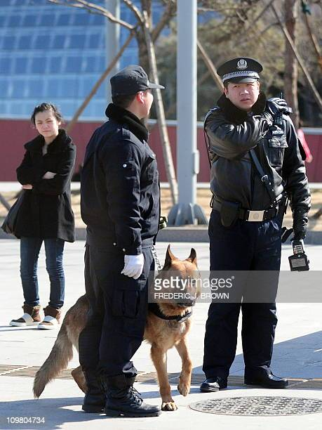 Policemen and a police dog walk on patrol along Chang'An Avenue near Tiananmen Square in Beijing on March 6 2011 amid heightened security with the...